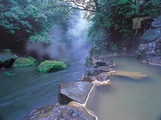 朝もやのすがすがしい渓谷沿いの露天風呂