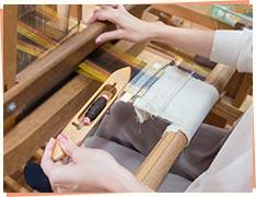 ④横の糸を通して、足で機織り機を押す。