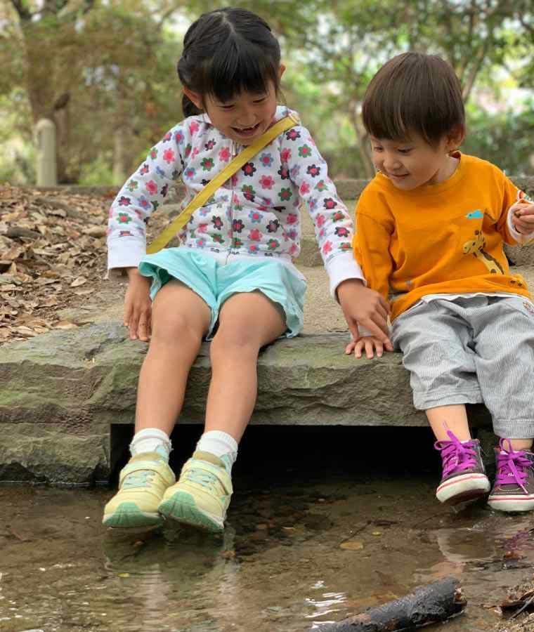 流れる小川で遊ぶ子どもたち
