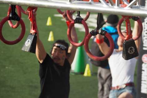 不安定な吊り輪をつかんで進む参加者