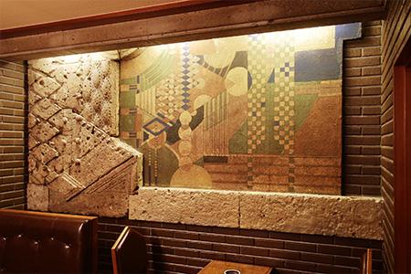 ライト館から移設された、大谷石のファサード。世界の建築史に名を刻む旧本館の面影を、最も感じられる場所だ。その手前には、マリリン・モンローが宿泊した部屋に置かれていたというテーブルセットも。